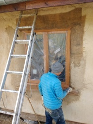 Placing the first coat of render over the hessianed reveal